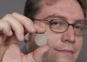 UC historian Robert Haug holds a late eighth-century coin from Baghdad. Medieval coins from Central Asia and the Middle East chronicle political, cultural and social shifts as Islam took root over several centuries. Photo by Dottie Stover, University of Cincinnati