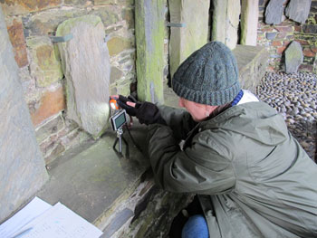 "Dr. Larissa ""Kat"" Tracy examines a Viking-age stone monument on the Isle of Man."
