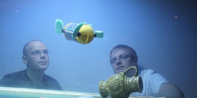 Researchers Asko Ristolainen and Taavi Salumäe looking the u-CAT swimming in an aquarium at Centre for Biorobotics