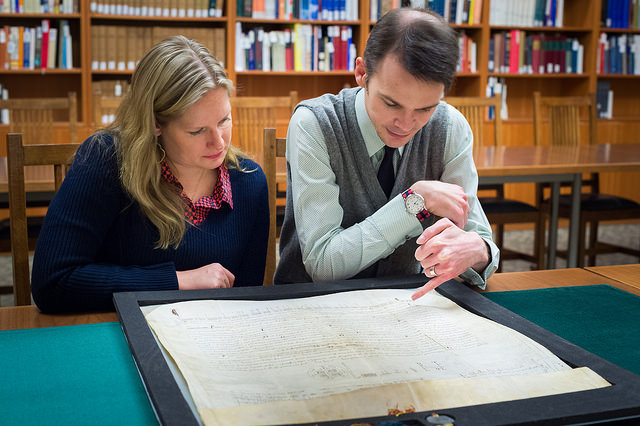 UBC's Katherine Kalsbeek and Richard Pollard admire the Papal bull acquired by UBC Library. The medieval document, written in 1245, is likely the oldest of its kind in Canada. Credit: Don Erhardt