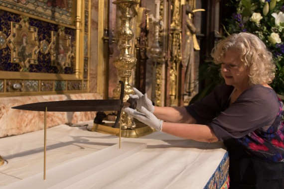 Diana Heath, Metalwork Conservator lays Henry V's sword on the High Altar at Westminster Abbey. Photo courtesy of Dean & Chapter of Westminster.